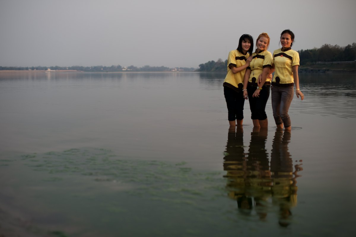 Three colleagues take a short evening break from work in Vientiane to cool off by the Mekong River and watch the sunset.