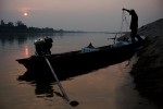 As night falls, a Laotian fisherman prepares to set his nets across the Mekong River.
