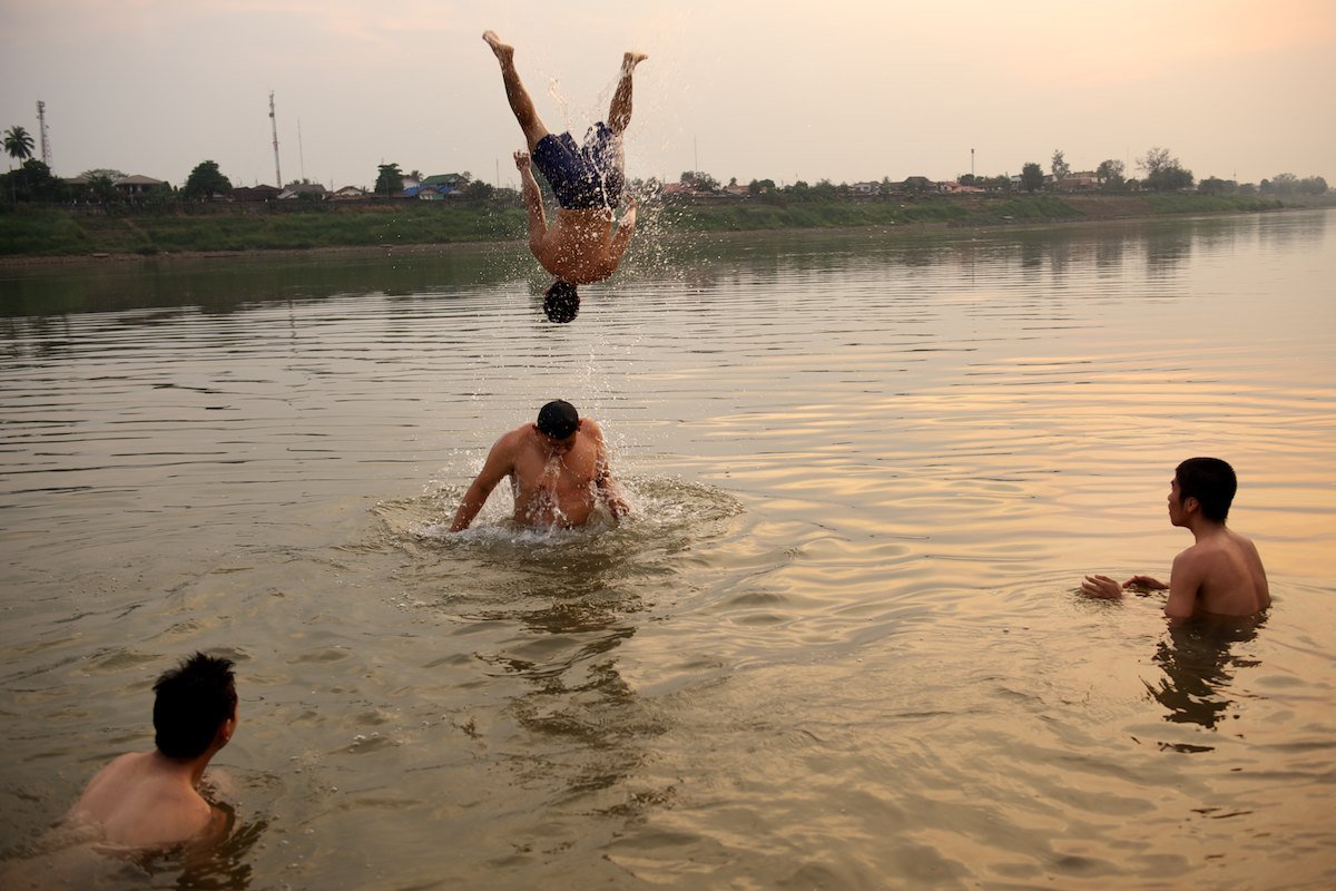At the end of the day a group of young men swim and cool off in the Mekong River.