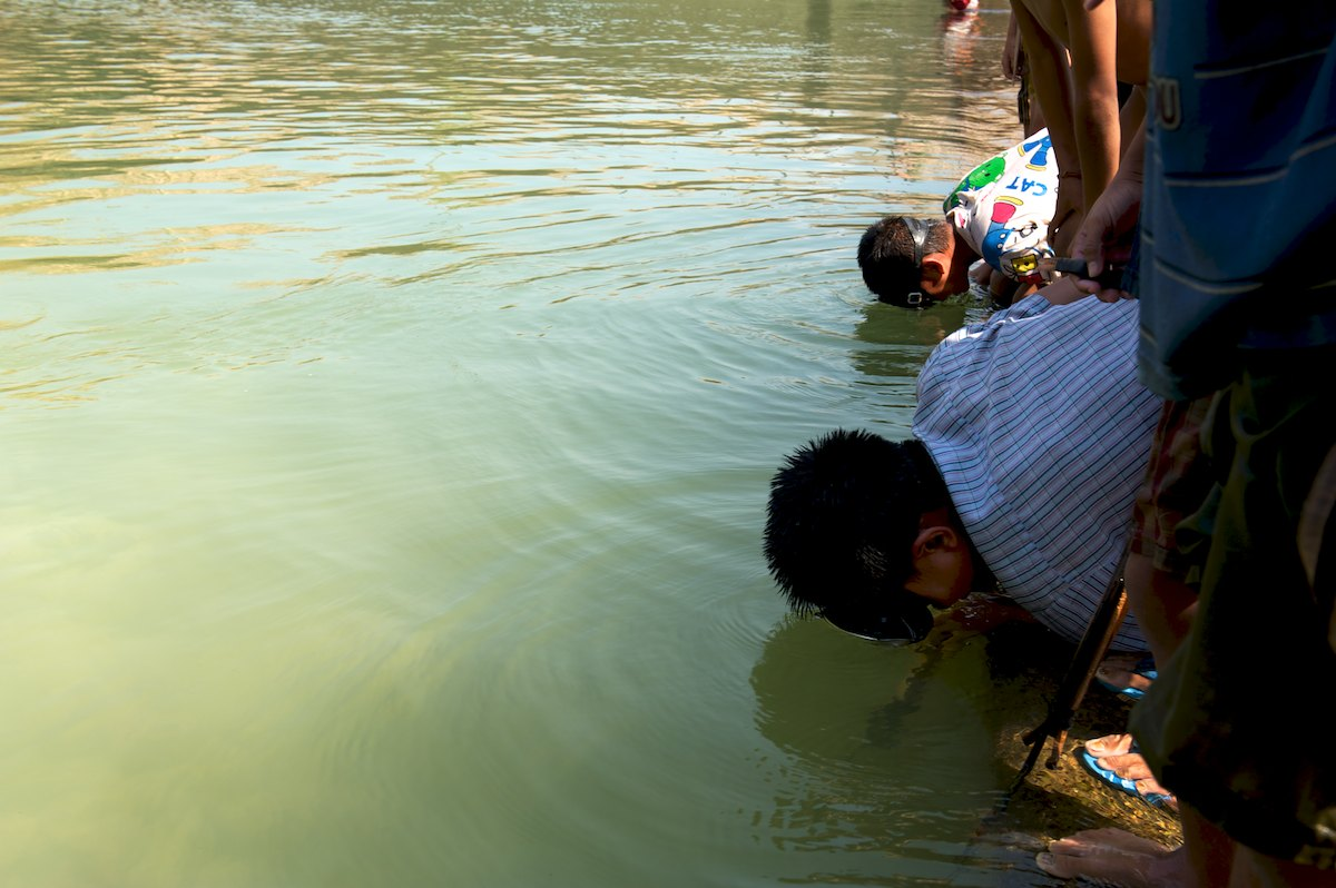 Children from Ban Khounkham look for fish to spear in a discharge pool at the base of the Theun-Hinboun Power Plant surge control pond regulating weir. Water is diverted from the Nam Theun/Nam Kading basin through the Theun-Hiboun Hydropower Plant tunnel system and into the Nam Hai/Nam Hinboun River basin to the south. Further downstream the Nam Hinboun River flows into the Mekong River.