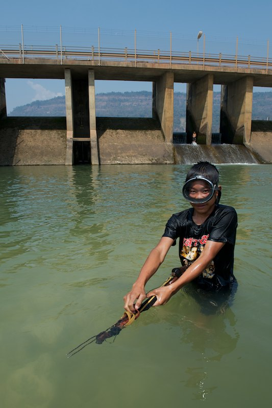 A young spear fisherman from Ban Khounkham hunts for fish in a discharge pool at the base of the Theun-Hinboun Power Plant surge control pond regulating weir. Water is diverted from the Nam Theun/Nam Kading basin through the Theun-Hiboun Hydropower Plant tunnel system and into the Nam Hai/Nam Hinboun River basin to the south. Further downstream the Nam Hinboun River flows into the Mekong River.