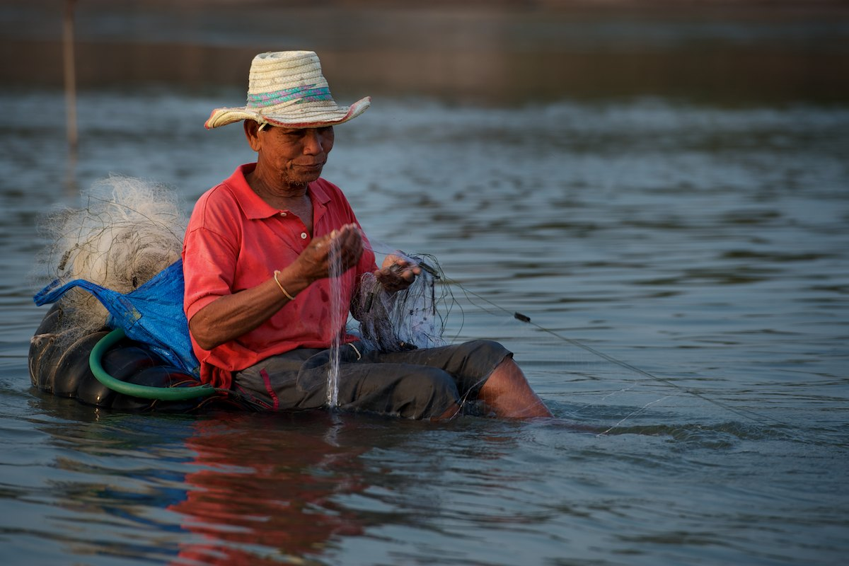 A fisherman utilizes a inflatable inner tube to help quietly set his nets and carry equipment as he fishes in the middle of the Mekong River.