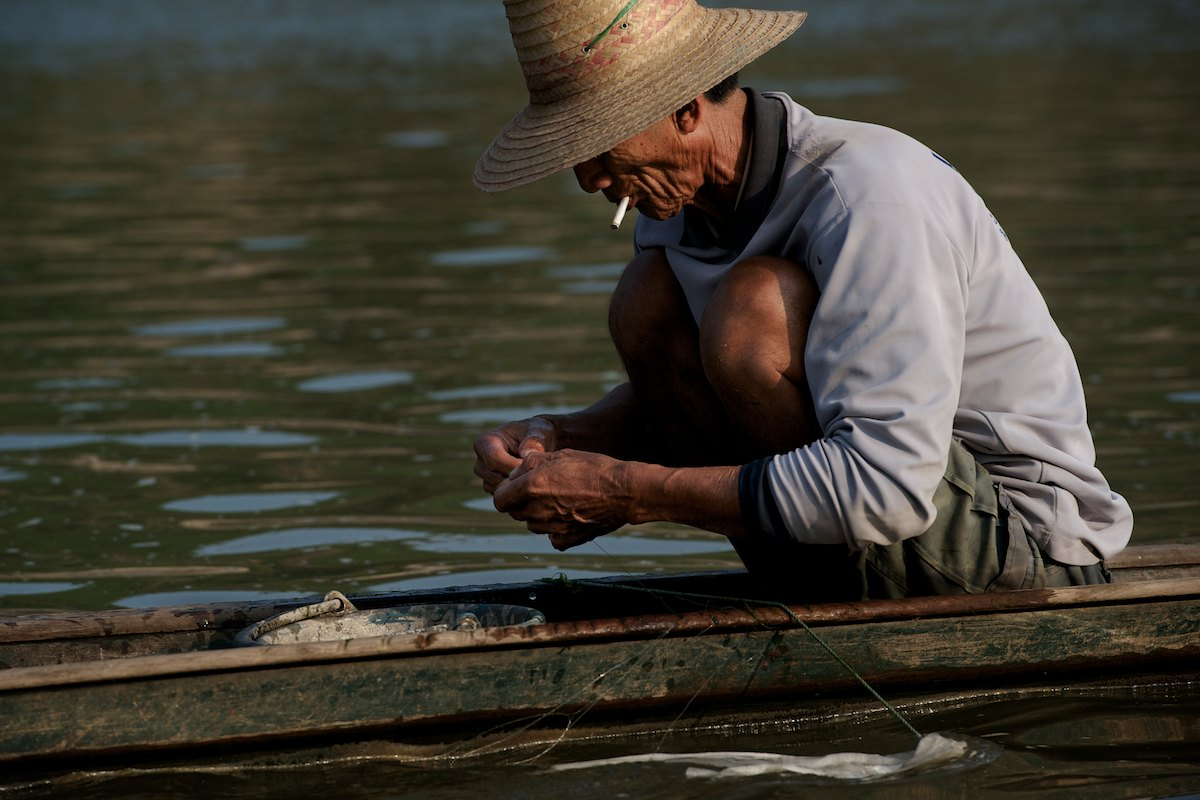 A fisherman checks and cleans his net near the proposed site of Pak Chom dam along the main course of the Mekong River.