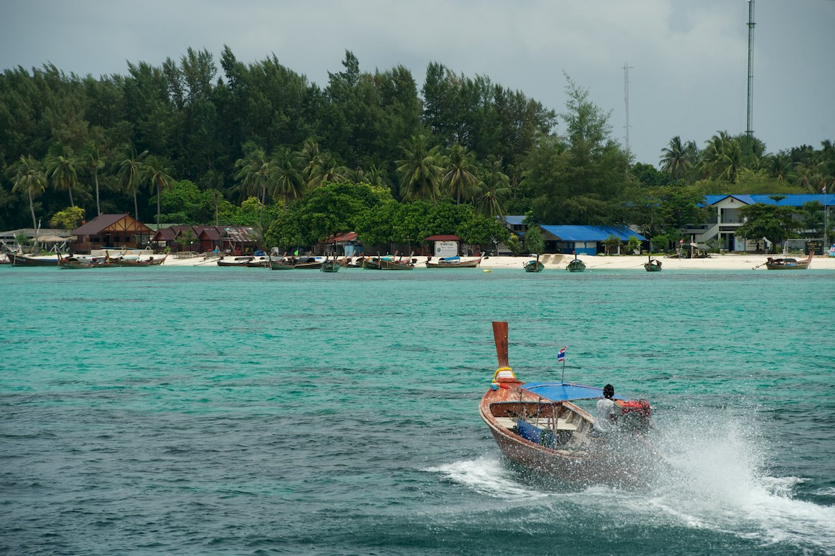 A longtail boat driver heads to shore. Longtail boats are used daily to shuttle tourists around the island and for various forms of fishing.