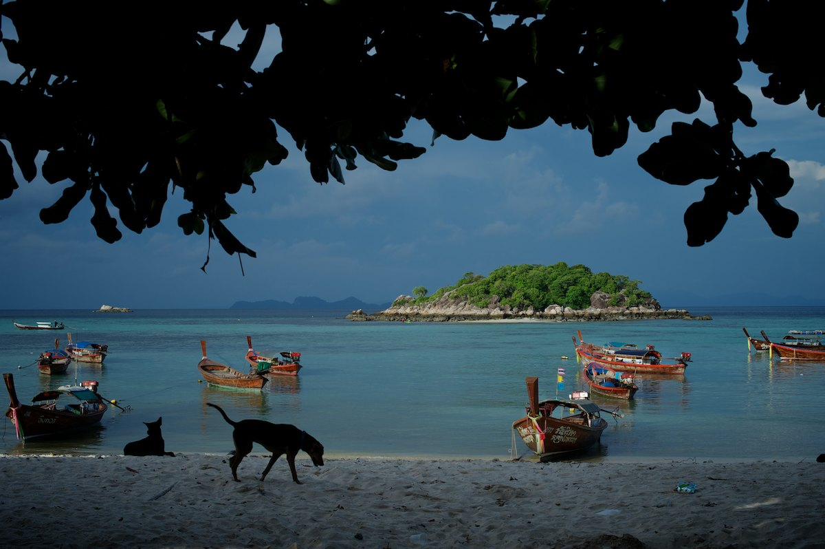 Longtail boats anchored off the shore of Sunrise Beach with Koh Kra island in the distance. Longtail boats are an essential part of the Urak Lawoi' material culture. In addition to being the main form of transportation, boats allow access to the archipelago's rich resource diversity and create monetary opportunities within the fishing and tourism industries.