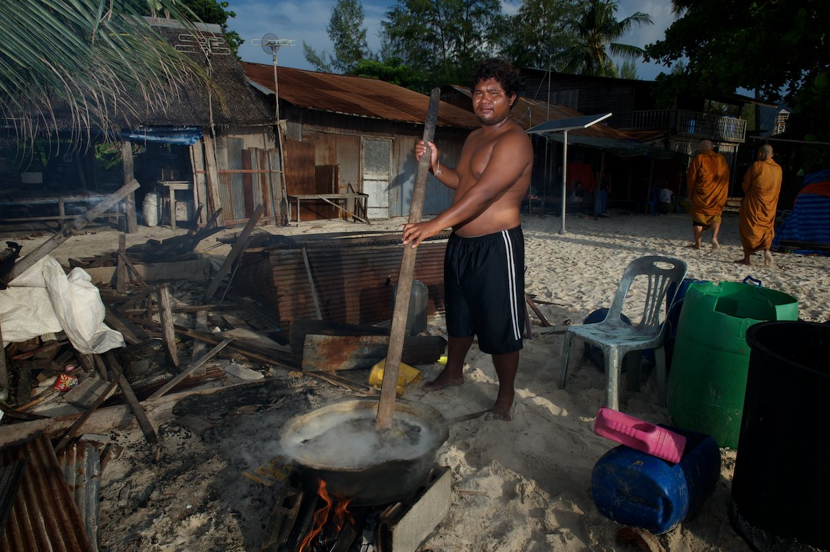 Chan boils sea cucumber outside his home. Prior to boiling, the night's sea cucumber catch is rinsed, gutted and cleaned using large plastic drums. Once boiled, the sea cucumber will be laid out over corrugated metal to dry in the sun and over a low fire.