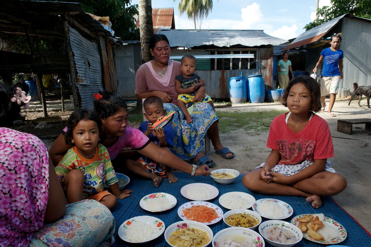 A group of Urak Lawoi' share a meal. Many Urak Lawoi' live among themselves in nuclear-type families, consider themselves kin, sharing resources and promoting each others success in times of need.