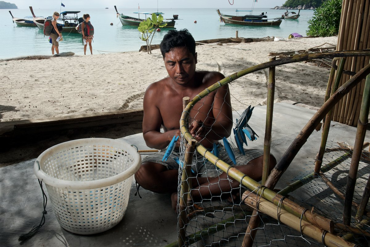 Mr. Korn, a local Urak Lawoi', trap fisherman constructs a small fish trap made out of rattan, steel wire and plastic. Trap fishing is practiced in the Adang Archipelago's near shore coral reef and rock environments at average depths of 10m to 20m.