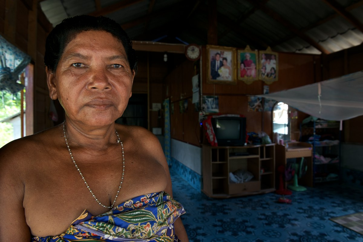 A portrait of Mai Kim in her home. Consumer goods are becoming more common in Urak Lawoi' homes, television sets, DVD players and mobile phones are common, typically desired by the younger generations.