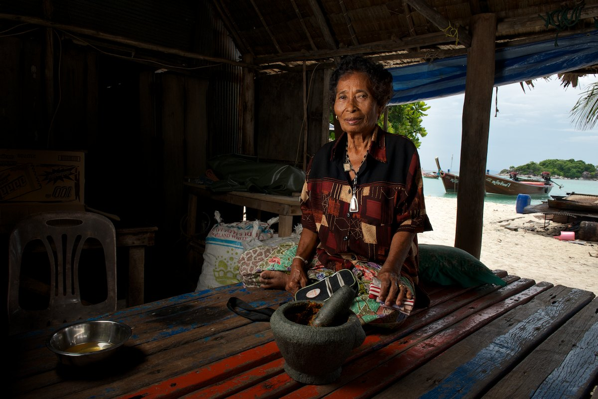 Ayun uses her mortar and pestle to mix curry paste on the porch outside her home on Sunrise beach. The Urak Lawoi' traditionally live in homes and villages on the beach and in the past would seasonally move locations on the island away from the prevailing winds.