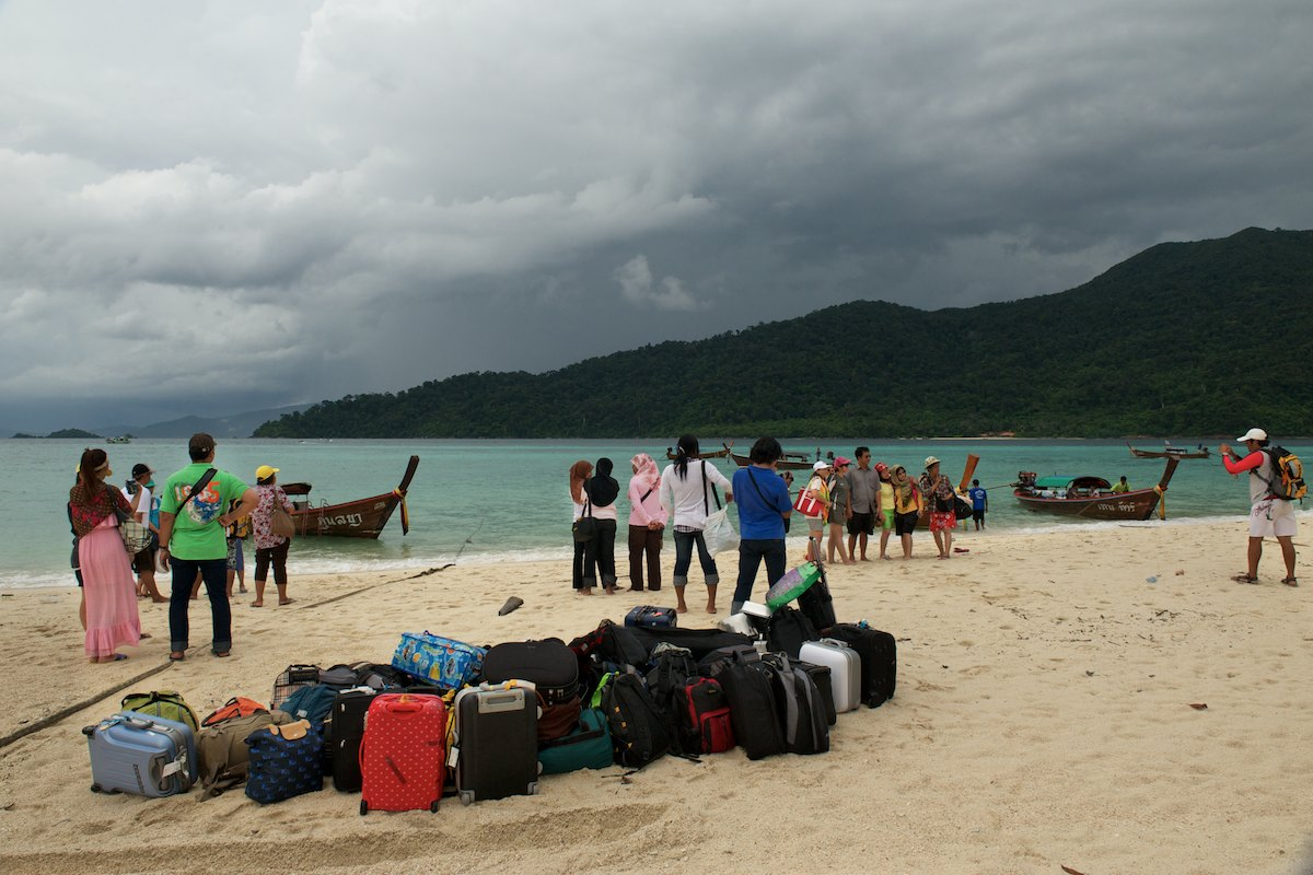Thai tourists from the Satun province prepare for their departure back to the mainland. Many Urak Lawoi' men now use their boats to shuttle tourists to and from resorts on Koh Lipe and to larger mainland ferry service operations docked offshore in deeper water.