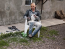 Potteryartist Goyin Silveira sitting in his yard sanding one of his pots.  Photo by Carlotta Boettcher 2011