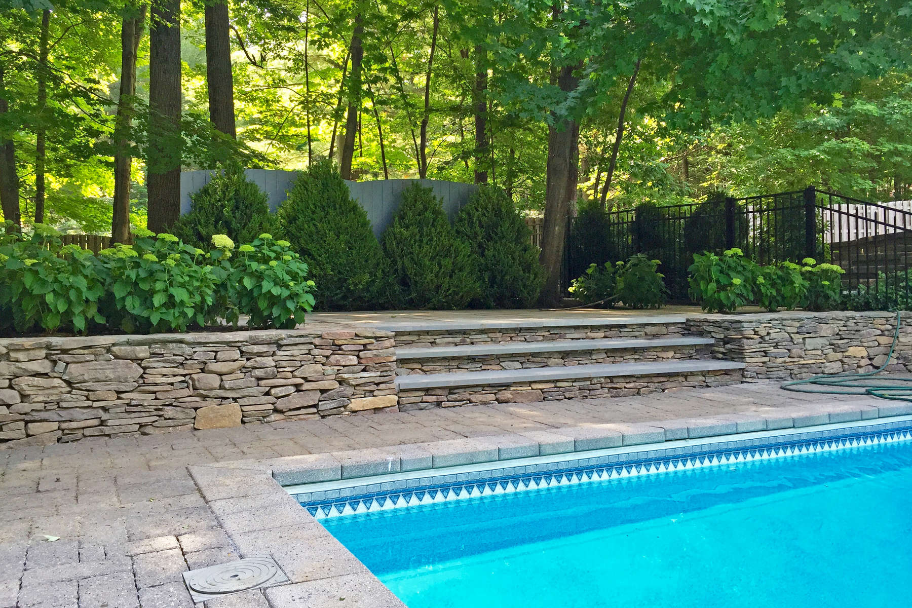 An elevated pool lounging area provides a focal vista to the pool and creates a shady garden room, which stays cool on the hottest of days.