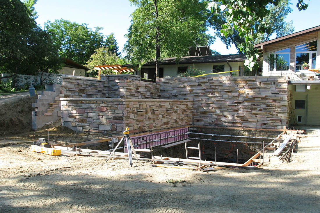 A site visit showing the inspection of a  pool, water feature, site grading and stone walls.