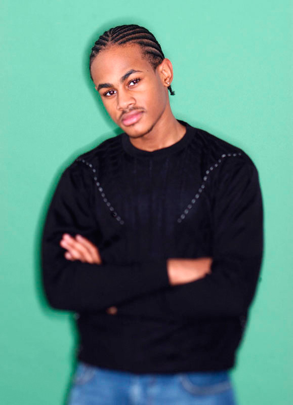 Studio portrait of an young Afro-American musician & rapper shot against a green background for a video.