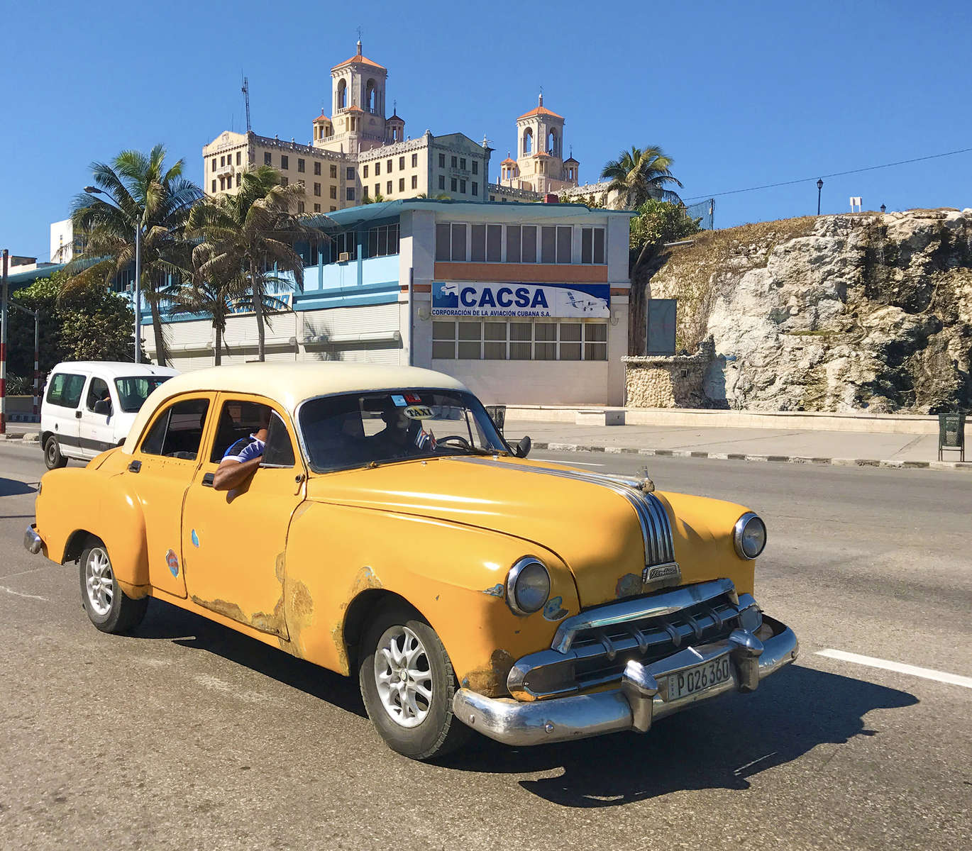Photo of Cuban youth driving a yellow, vintage Pontiac on the Malecon Drive in Havana, Cuba.