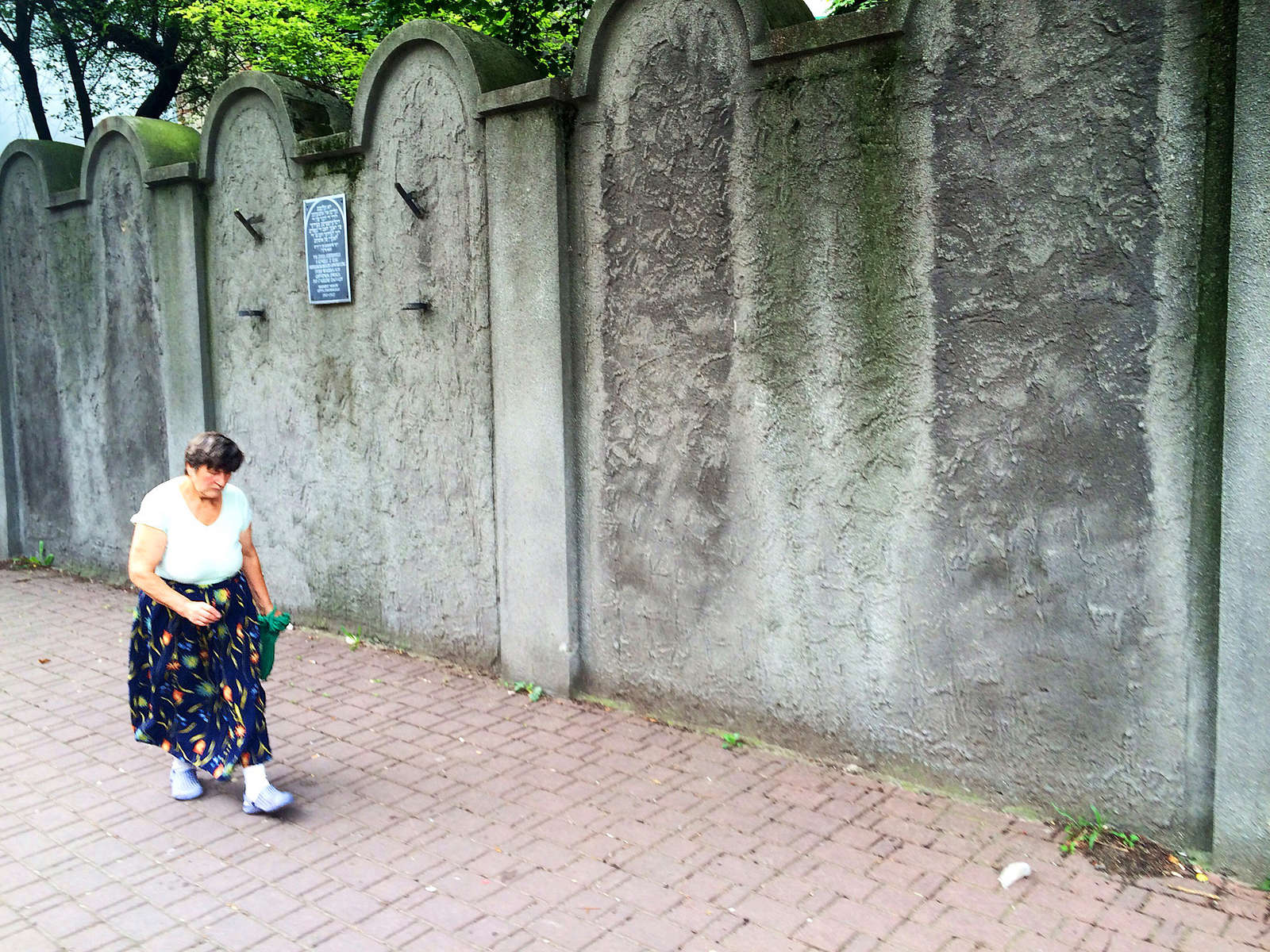 A woman walking by Jewish Ghetto wall, Poland