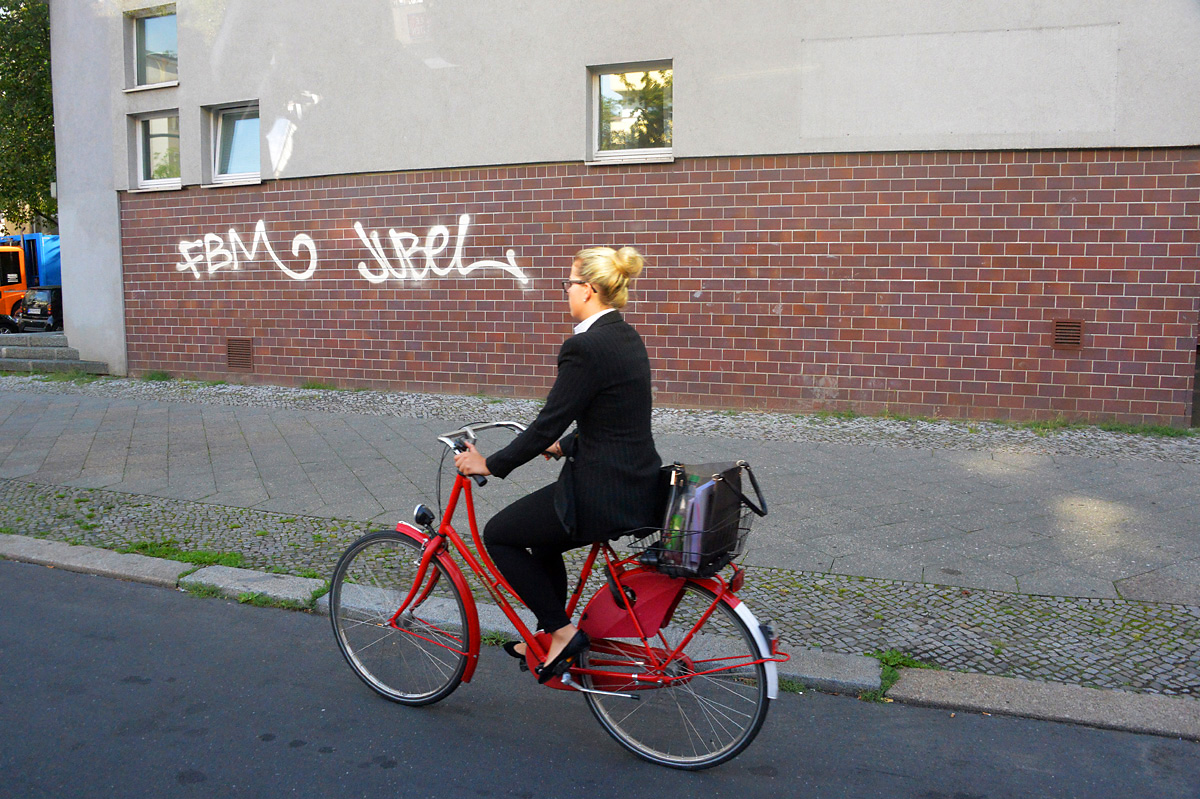 Lifestyle photo of a young blonde woman riding a red bicycle in Berlin, Germany with grafitti on a wall next to her.