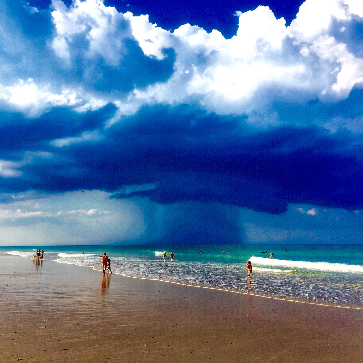 A photo of a beach in Cape Cod, MA showing a storm brewing in the sky. There are people walking along the shoreline in the distance