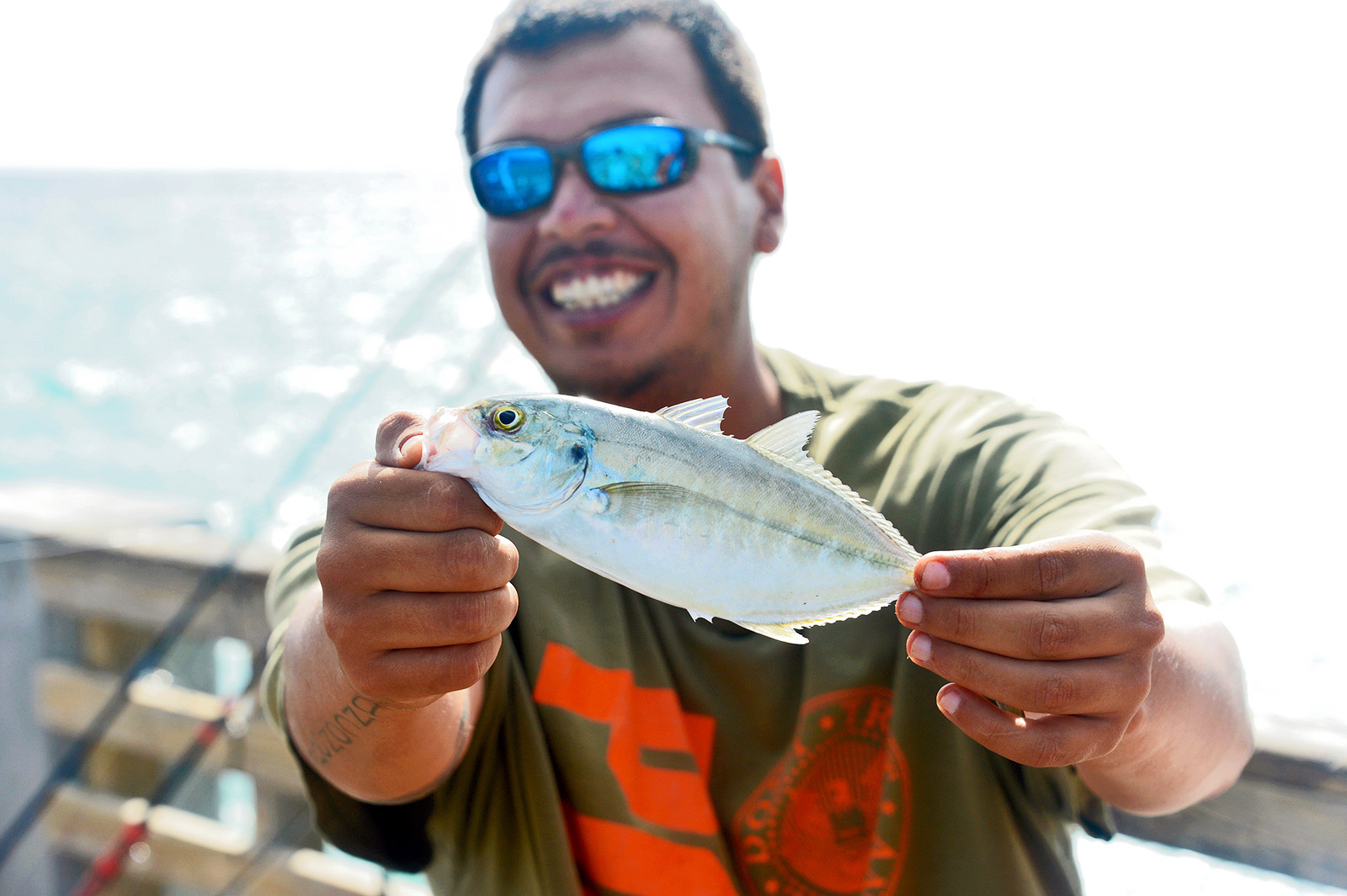 A lifestyle photo of a man with sunglasses- smiling as he shows off a small fish he caught on the pier in West Palm beach, Florida.