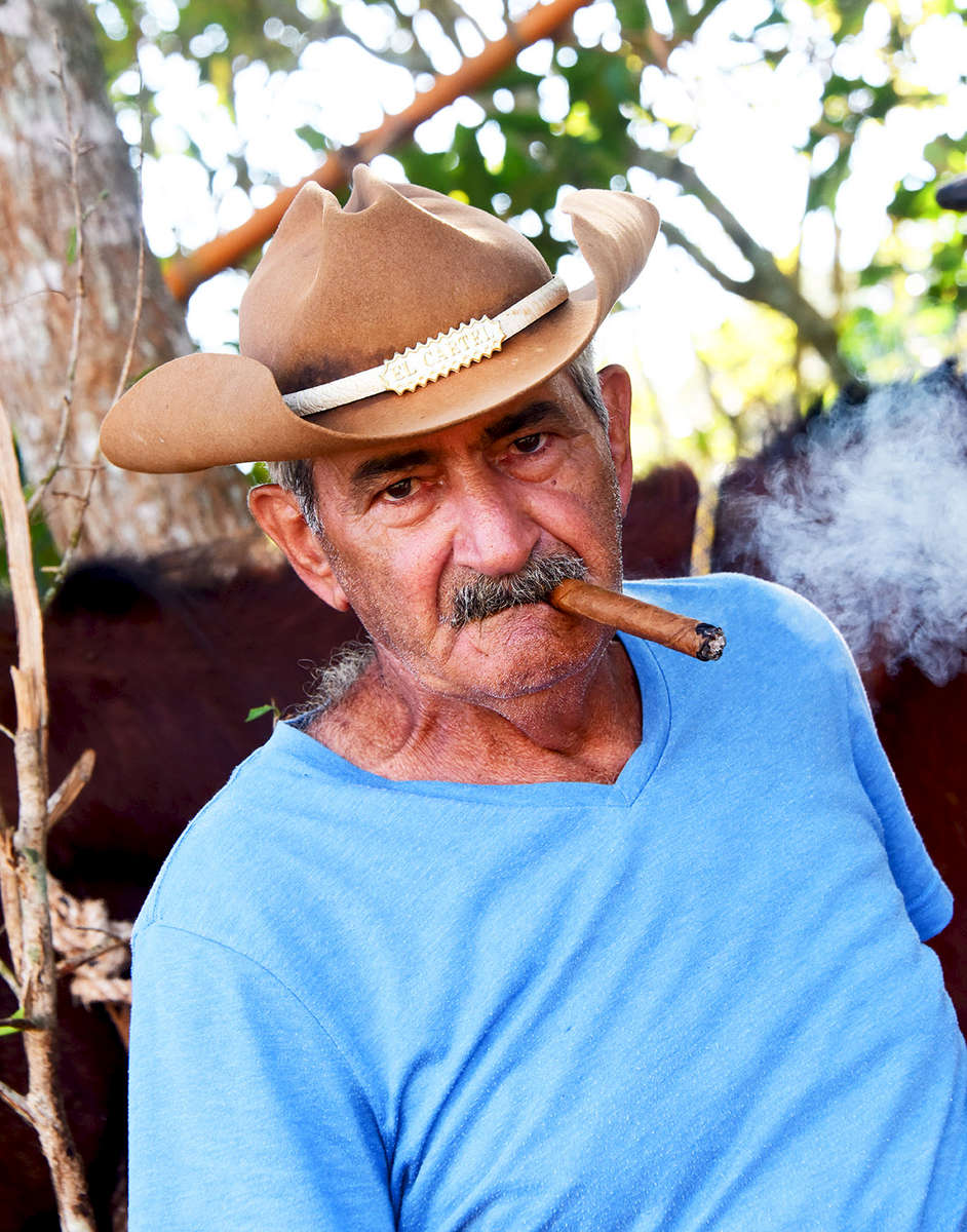 Portrait of a Cuban tobacco farmer in Viñales, Cuba smoking a cigar with his horse behind him.