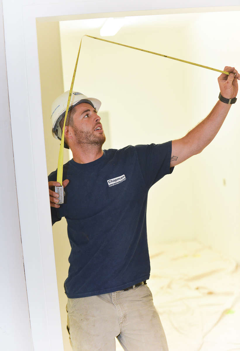 A lifestyle photo of a Chapman Construction supervisor measuring a door.