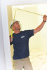 This ia a lifestyle photograph of a Chapman Construction Design supervisor measuring a door at a job in Brighton, MA