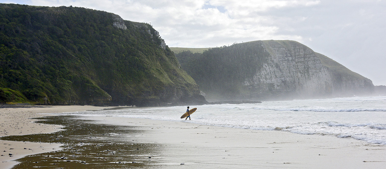 This is a lifetyle photo of a lone surfer with his board walking along the shore on the Wild Coast of South Africa on a foggy day with mountains in the background.