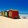 A lifestyle photo of changing rooms at Surfers Corner beach in Muizenberg, South Africa with people sitting in the sun.