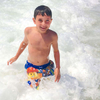 Lifestyle photo of a happy young boy in a swinsuit coming out of the ocean's surf in Cape Cod, MA