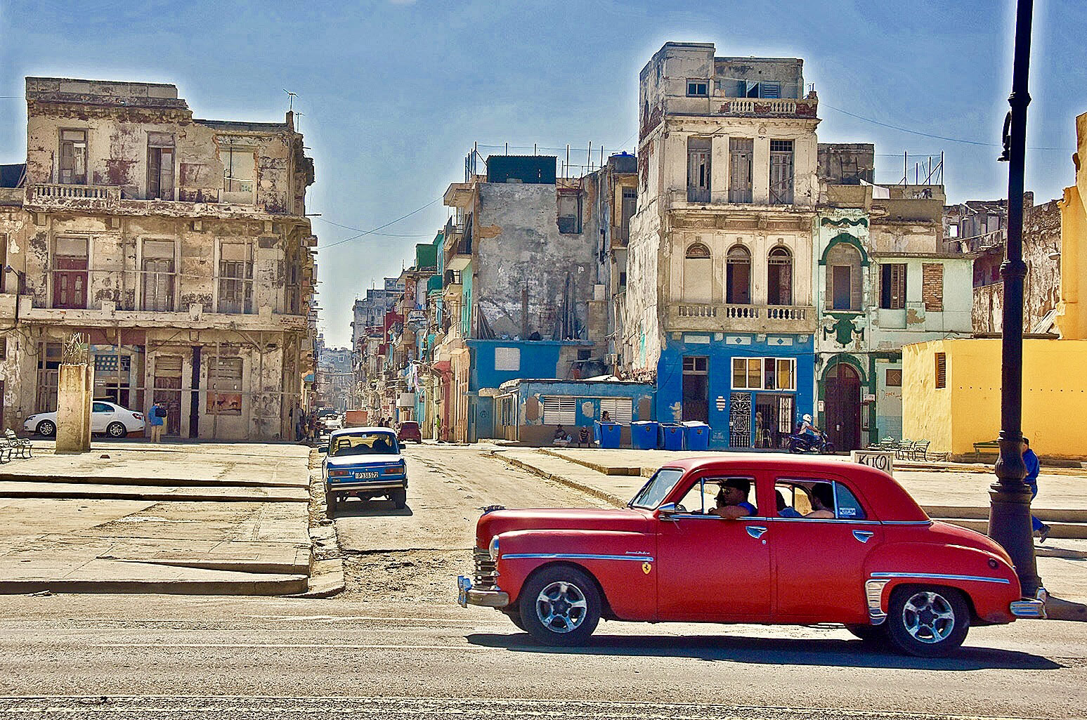 Photo of a classic old red car going down the Malećon Drive in Havana, Cuba showing desolate buildings in the background.