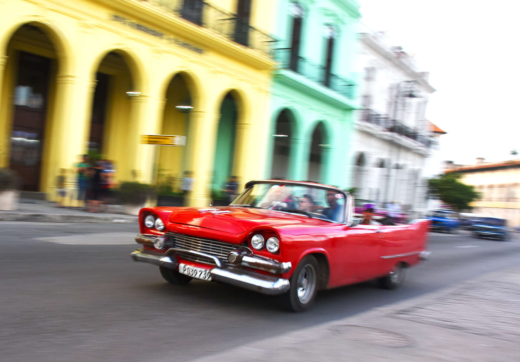Photo of young people driving a red car with colorful buildings in the background in Old Havana, Cuba.