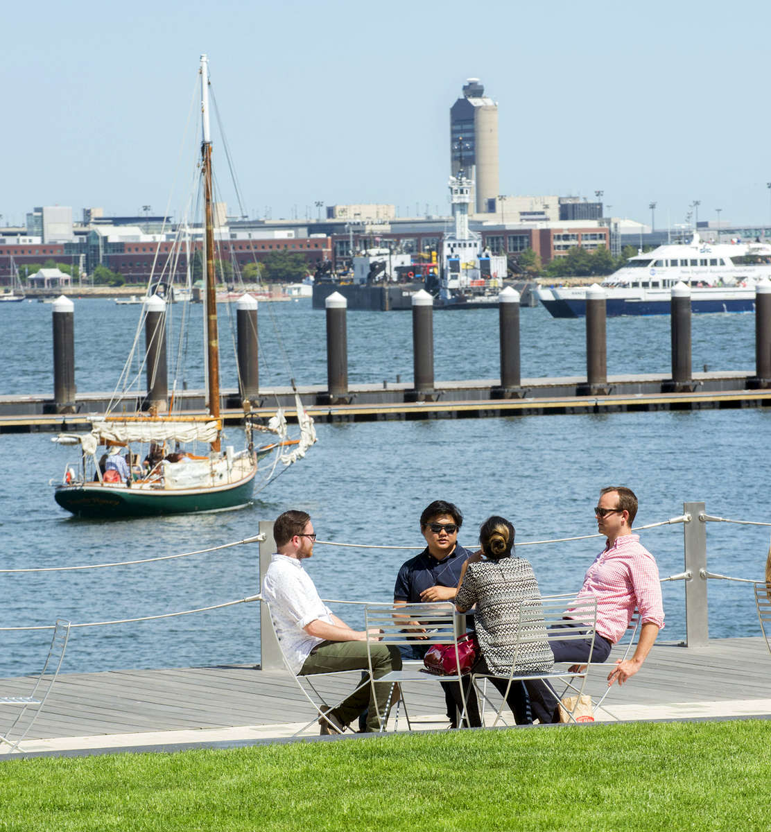 A lifestyle photograph of people talking at a table in a park in the Seaport district, Boston, MA on a sunny day with boats in the background.