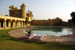 This is a lifestyle photo shot at sunset in Rajasthan, India showing a former palace of a Maharajah that is now a hotel. There is a lone man reading a book by a pool.