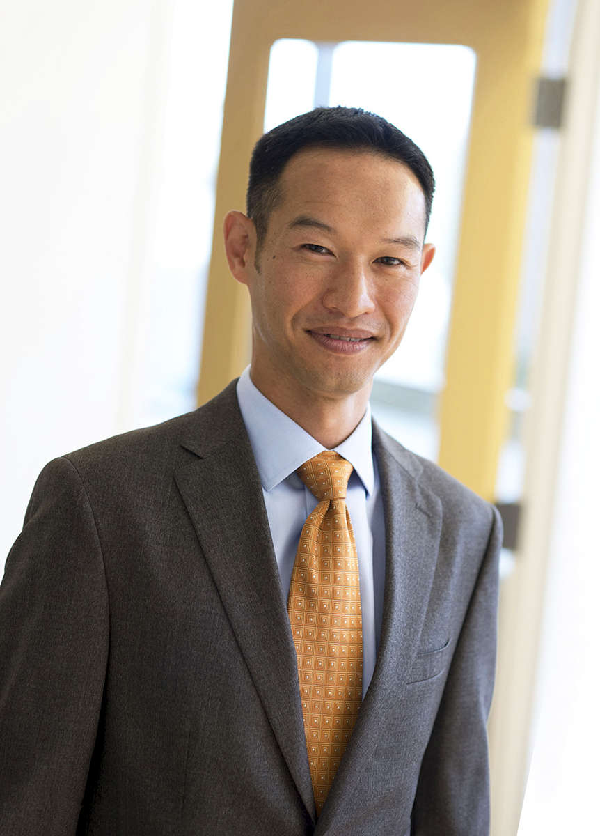 A casual portrait of an Asian American executive engineer for a web site photographed with a window behind him.