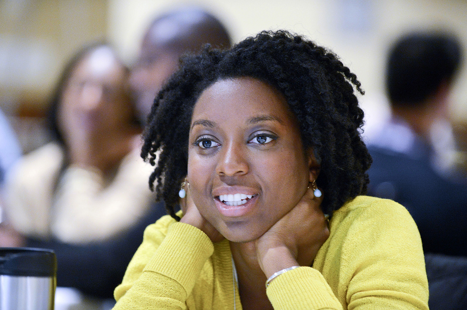 An Afro- American woman business student in a yellow sweater listening to a speaker leading a panel discussion in Boston, MA