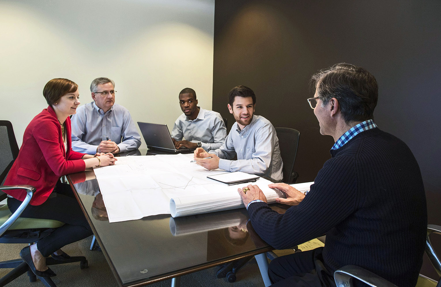 This is a lifestyle photo of four men and a woman talking at a table in a conference room at Cannistraro Company.