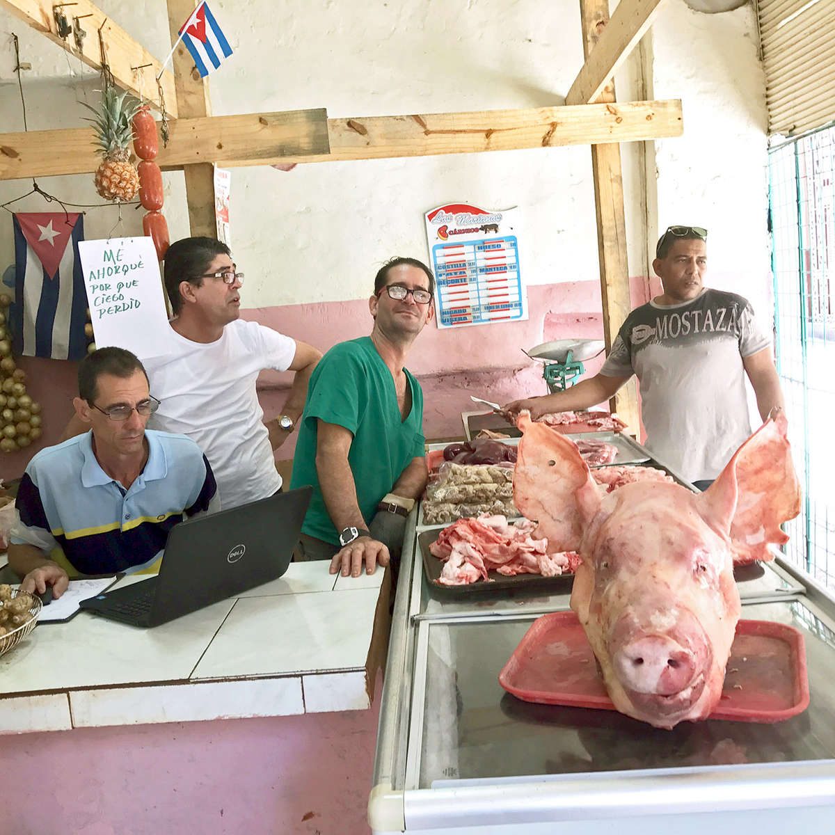 Photo of men selling fresh killed pork inside a butcher shop in Old Havana, Cuba.