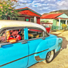 Photo of a Cuban couple driving their vintage 1952 Chevy in Viñales Valley, Cuba with colorful houses in the background.