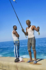 A photo of two Cuban fisherman holding their fish on the Malecón Seawall in Havana, Cuba.