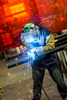 A lifestyle photo of a man at work welding pieces of steel together showing colorful sparks coming from his tool.