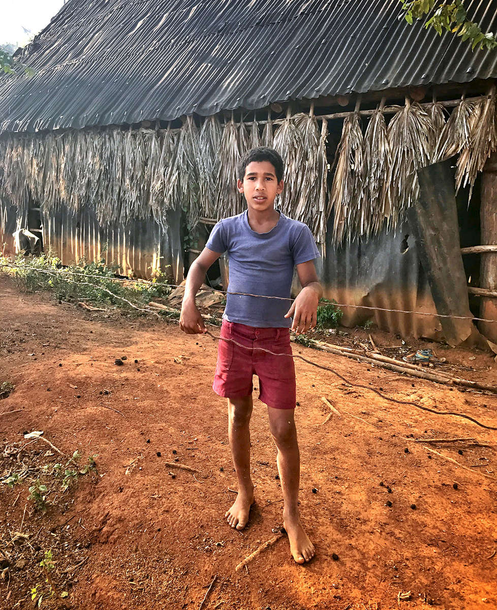 Photo of a tobacco farmers son standing in front of a tobacco drying barn in Viñales Valley, Cuba.