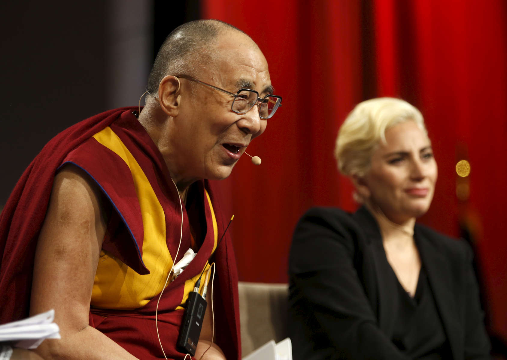 The Dalai Lama chuckles during a panel featuring himself and Lady Gaga during The United States Conference of Mayors in Indianapolis, Indiana Sunday June 26, 2016.