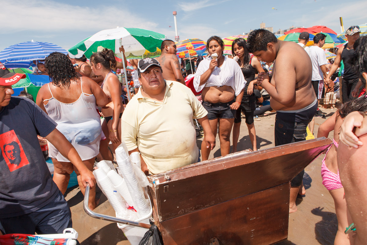 An estimated 75,000 people visited Coney Island on July 4th weekend, 2010. Food vendors cruise the east-west thoroughfare maneuvering their carts through the crowds at water's edge.