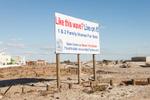 A sign advertising new condos for sale survives Hurricane Sandy, Rockaway, Queens. November 4, 2012.