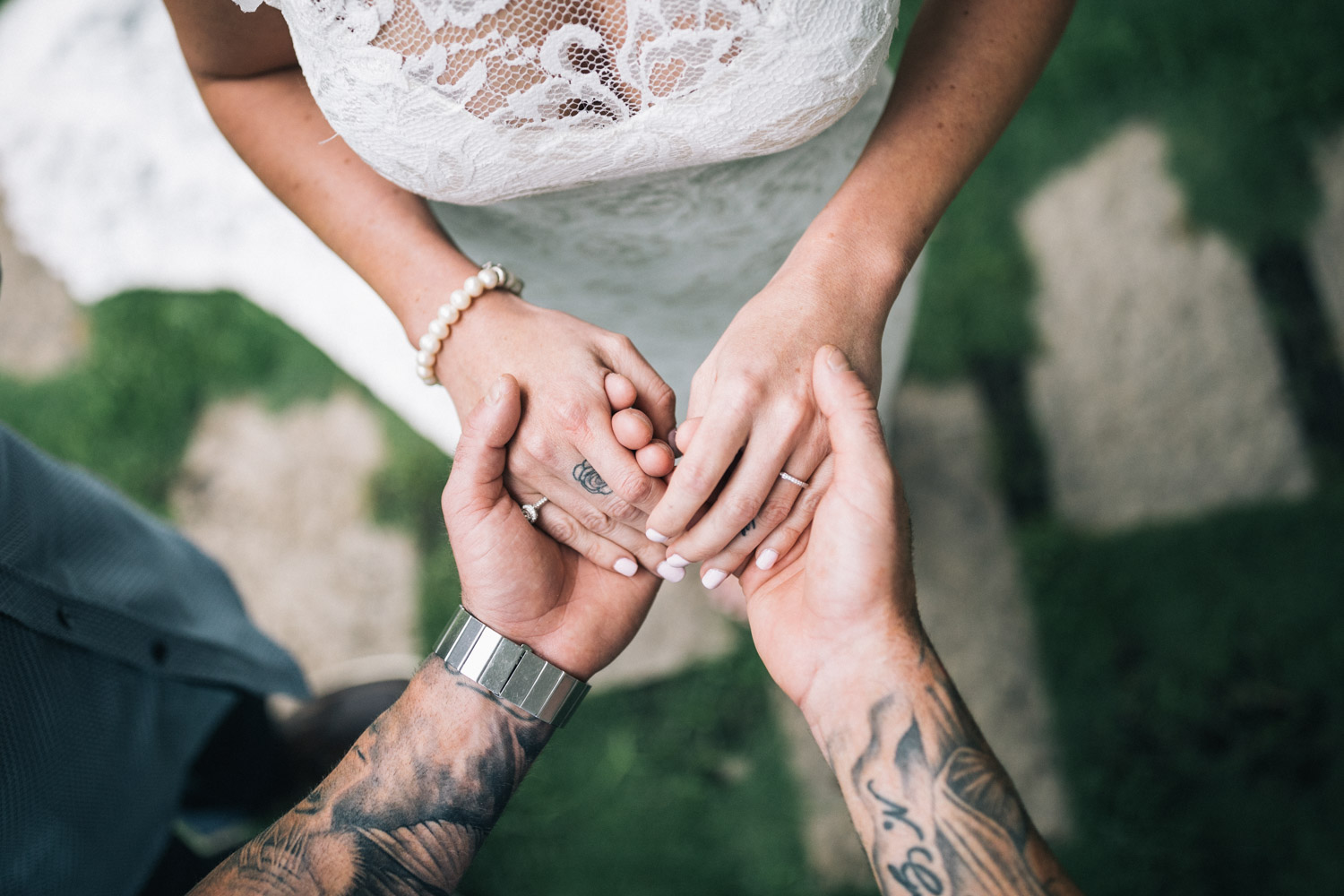 A tattooed husband and wife excchange wedding rings during a garden ceremony.