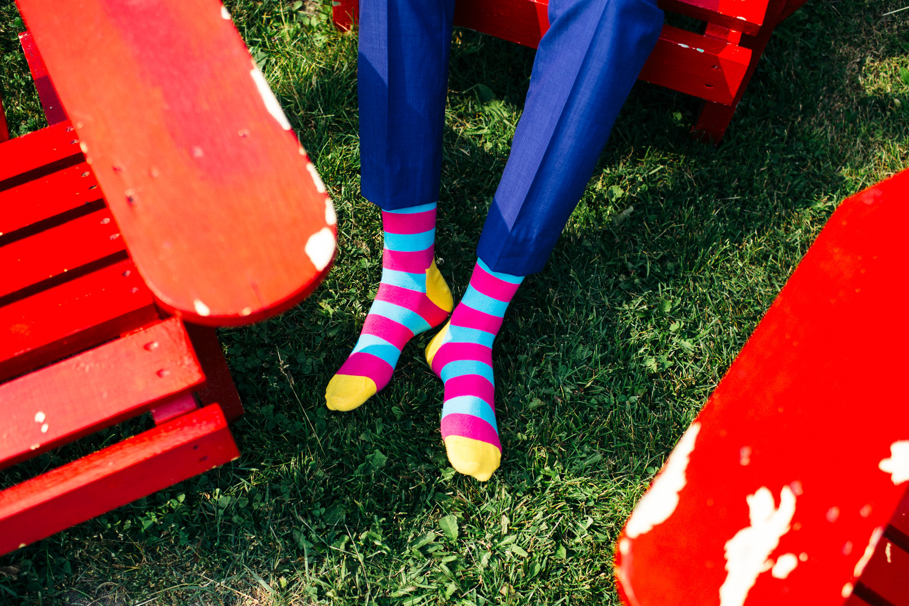 Colorful socks on a grass lawn with red chairs during summer in Nova Scotia, Canada.