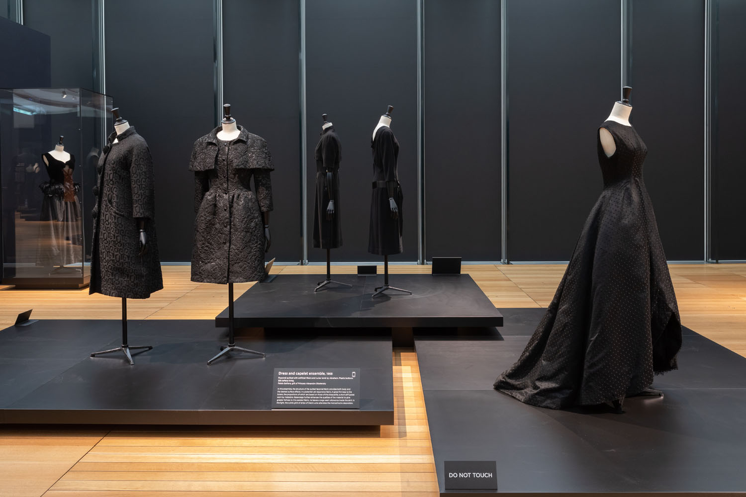 Balenciaga in Black at the Kimbell Museum was an overview of couturier Balenciaga' s career from the 1940s to the 1960s. Over 100 pieces of hand made dresses were featured, including gowns, suits and accessories, all black. The goal of the exhibition design was to accentuate the various shapes, volumes, textures, and silhouettes of Balenciaga' s timeless creations, and to encourage visitors to examine the exquisite detail in his work. Freestanding cases allowed for 36 0 degree, close-up viewing of the pieces, while cascading platforms enabled the composition of dramatic tableauxs.