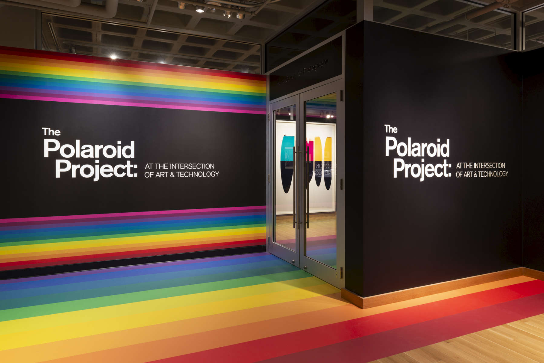 "The Polaroid Project: At the Intersection of Art and Technology was an exhibition in two adjacent gallery spaces that explored various dimensions of the relationship between the art and technology of Polaroids, with over 200 photographs and 100 objects. To unite the two galleries, and the art and the technology, the iconic Polaroid spectrum rainbow logo was translated into a continuous spine through the centerline of the exhibition, tying together the 2 gallery spaces, display cases, immersive seating, and a connecting wall. The display cases featured artifacts including prototypes, components, and cameras tracing the Polaroid company's many technological innovations over time. Photographs were displayed on ""baffle"" walls inspired by the interior of a 20x24 large format instant camera, which was also prominently displayed in the exhibition."