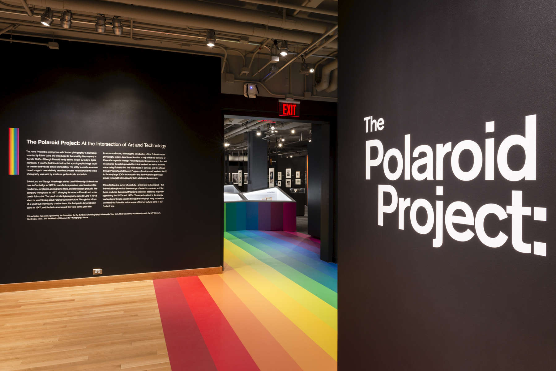 """The Polaroid Project: At the Intersection of Art and Technology was an exhibition in two adjacent gallery spaces that explored various dimensions of the relationship between the art and technology of Polaroids, with over 200 photographs and 100 objects. To unite the two galleries, and the art and the technology, the iconic Polaroid spectrum rainbow logo was translated into a continuous spine through the centerline of the exhibition, tying together the 2 gallery spaces, display cases, immersive seating, and a connecting wall. The display cases featured artifacts including prototypes, components, and cameras tracing the Polaroid company's many technological innovations over time. Photographs were displayed on """"baffle"""" walls inspired by the interior of a 20x24 large format instant camera, which was also prominently displayed in the exhibition.Visit the VR tour here."""